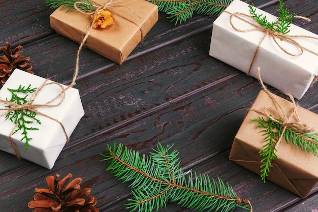 Weihnachtszusammensetzung. weihnachtsgeschenk, gestrickte decke, tannenzapfen, tannenzweige auf hölzernem hintergrund.
