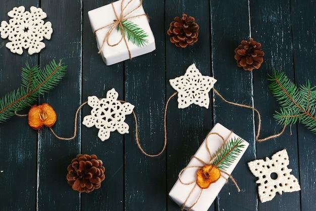 Weihnachtszusammensetzung. weihnachtsgeschenk, gestrickte decke, tannenzapfen, tannenzweige auf hölzernem.