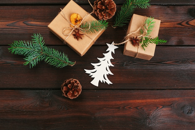 Weihnachtszusammensetzung. weihnachtsgeschenk, gestrickte decke, tannenzapfen, tannenzweige auf holztisch.