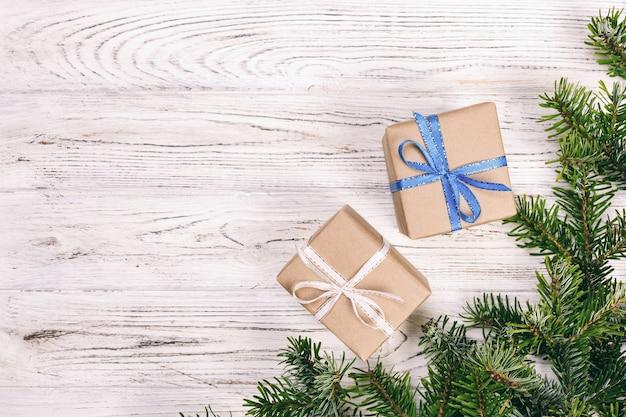 Weihnachtszusammensetzung. weihnachtsgeschenk mit tannenzapfen und tannenzweigen auf hölzernem hintergrund. flache lage, draufsicht, copyspace. getönten