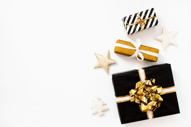 Weihnachtszusammensetzung. weihnachtsgeschenke, schwarzes und goldenes packpapier auf weißem hintergrund