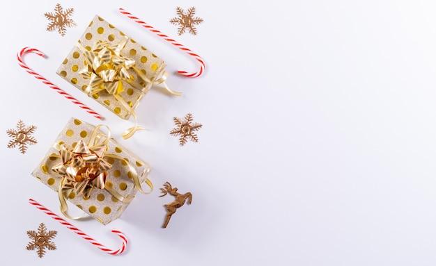 Weihnachtszusammensetzung. weihnachtsgoldgeschenkboxen, zuckerstange und golddekorationen auf weiß. draufsicht, kopie, raum