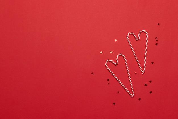 Weihnachtszusammensetzung. zuckerstangen in liebesform und sterne auf rotem hintergrund. weihnachten, winter, neujahrskonzept. flachgelegt, draufsicht