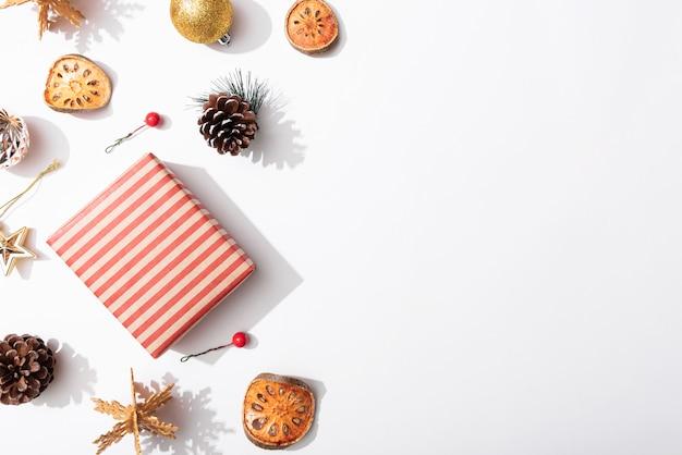 Weihnachtszusammensetzungshintergrund mit dekorationen und geschenkbox auf weißem hintergrund. winter, neujahrskonzept. flache lage, draufsicht, kopienraum.