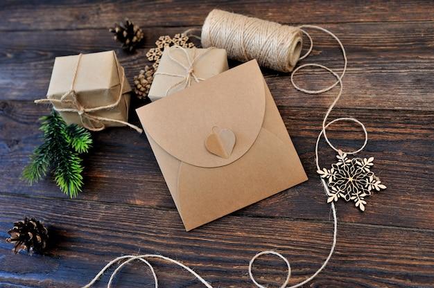 Weihnachtszusammensetzungssatz geschenkkraftpapierkästen, textilspielwaren und seil auf hölzernem hintergrund