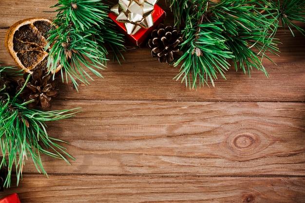 Weihnachtszweig mit kleinem kasten auf hölzernem brett