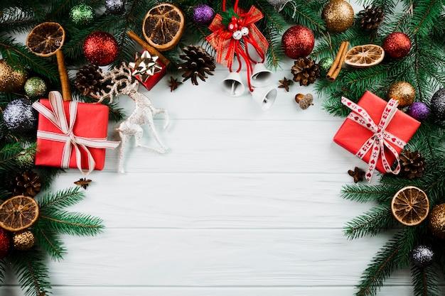 Weihnachtszweig mit rotwild und anwesenden kästen
