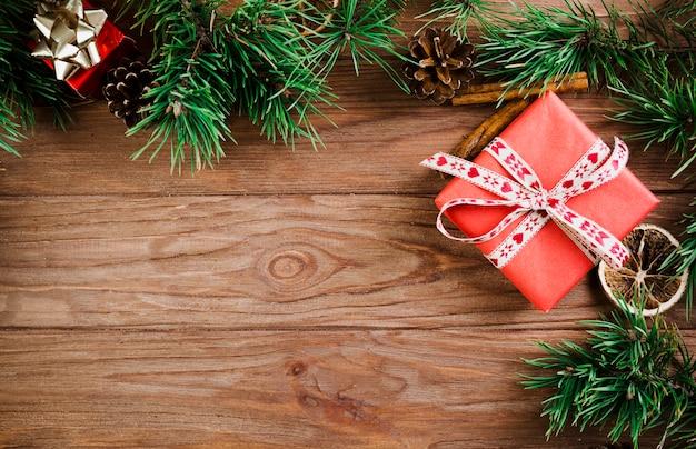 Weihnachtszweig und präsentkartons auf hölzernem brett