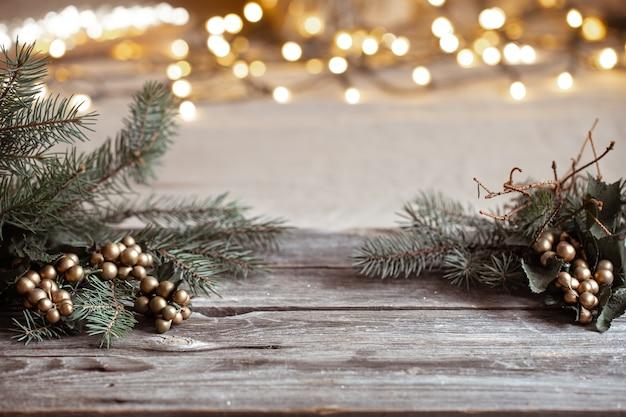 Weihnachtszweige eines weihnachtsbaumes auf einem holztisch und verschwommenen bokehlichtern.