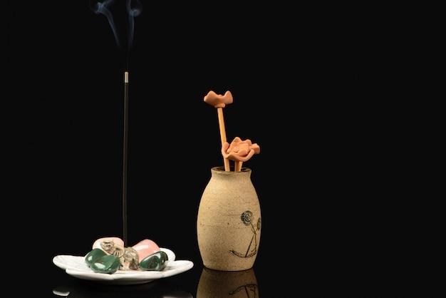 Weihrauch mit elefanten und steinen und keramikvase auf schwarz