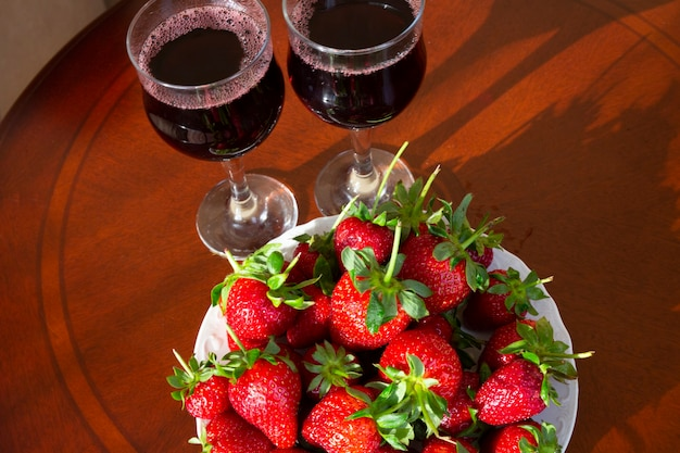 Wein aus beeren. frische reife erdbeeren und gläser rotwein im hintergrund. alkoholische getränke im sommer