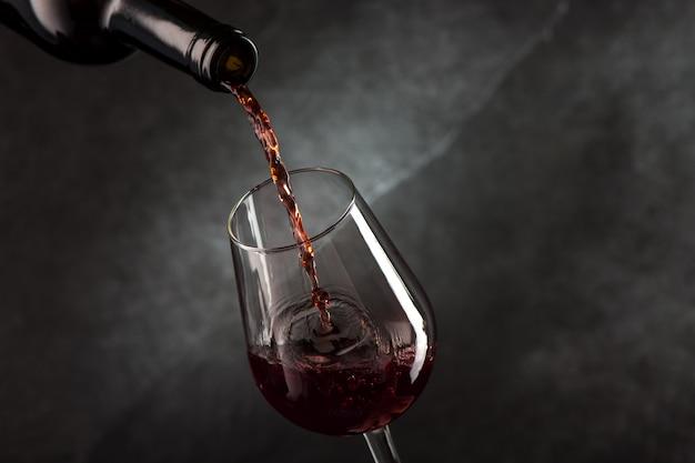 Wein aus der flasche in das glas gießen
