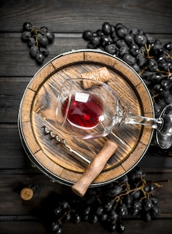 Wein. fass mit rotwein und trauben. auf einem holz.