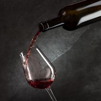 Wein gießt in glas aus der flasche