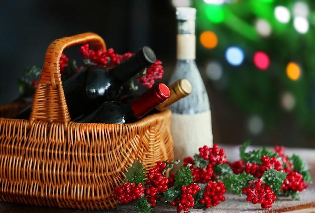 Wein im korb auf verschwommener weihnachtsbaumoberfläche