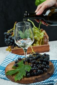 Wein in das glas mit traubenteller auf weißem tisch gießen