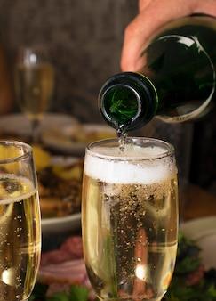 Wein in ein glas gießen. mann gießt bei einer feier champagner in ein glas, nahaufnahme