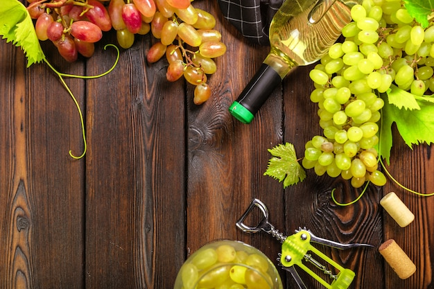 Wein mit zweigen der weißen trauben. auf einem holztisch.