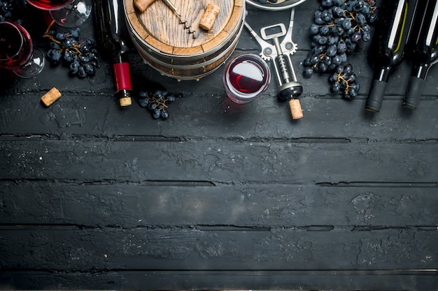 Wein. rotwein mit trauben und einem alten fass. auf einem schwarzen rustikalen.