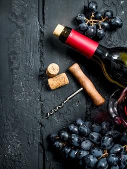 Wein. rotwein mit trauben und korkenzieher. auf einem schwarzen rustikalen.