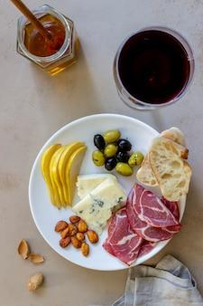 Wein snack. schinken, parmaschinken, mandeln, oliven, baguette, blauschimmelkäse. antipasti.