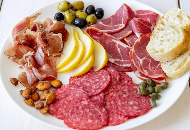 Wein snack. schinken, parmaschinken, salami, mandeln, oliven, baguette. antipasti.