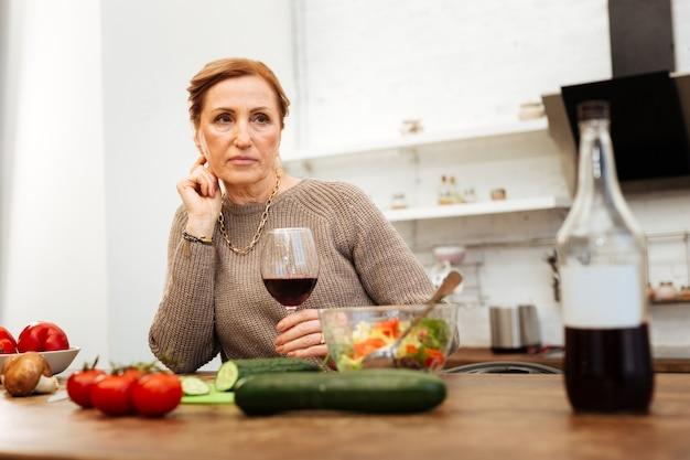 Wein trinken. einsame, gut aussehende erwachsene frau, die den abend in der küche verbringt, während sie sich ein gesundes abendessen macht