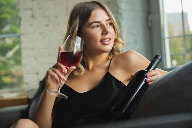 Wein trinken, sieht fröhlich aus. porträt des hübschen jungen mädchens in der modernen wohnung morgens.