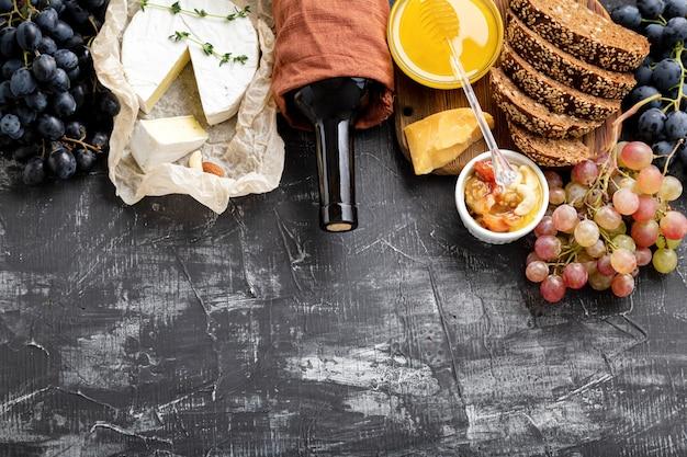 Wein- und käsekomposition. mediterrane küche gastronomie vorspeise rotweinflasche. lebensmittelsnacks zutaten verschiedene käsesorten trauben honigweinbrot auf dunklem betonhintergrund mit kopierraum.