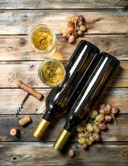 Wein. weißwein mit zweigen frischer trauben. auf einem holz.