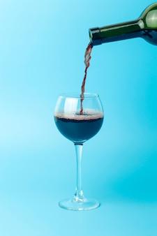 Wein wird in ein glas gegossen. rotwein wird zur verkostung in ein glas gegossen, minimales konzept.