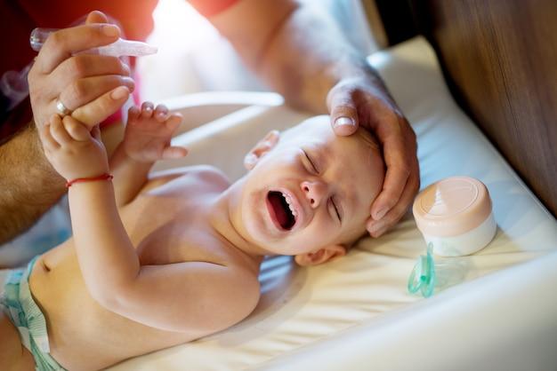 Weinen schönes baby, das auf dem bösen mit einem schnuller und einer creme nahe dem kopf liegt und sich weigert, nasentropfen zu bekommen.