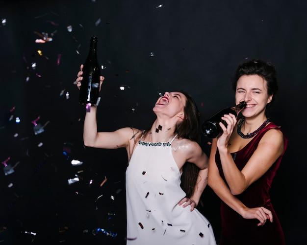 Weinende damen im abendkleid mit getränkeflaschen zwischen konfetti werfen