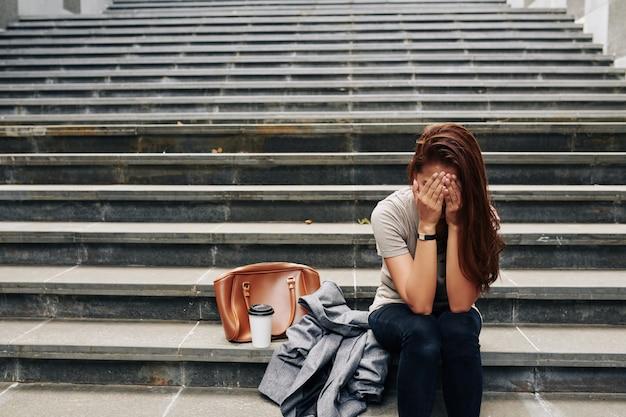 Weinende frau, die auf stufen sitzt