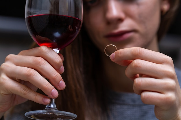 Weinende, geschiedene frau, die einen ehering hält und betrachtet und ein glas rotwein wegen ehebruchs, verrats und gescheiterter ehe trinkt