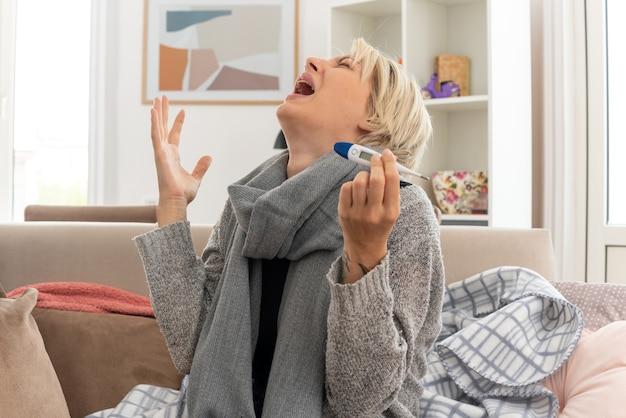 Weinende junge kranke slawische frau mit schal um den hals, die ein thermometer hält und auf der couch im wohnzimmer sitzt