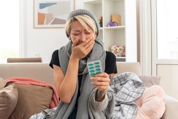 Weinende junge kranke slawische frau mit schal um den hals, die eine wintermütze trägt, die ihre hand auf den mund legt und die medikamentenblisterpackung auf der couch im wohnzimmer hält