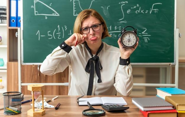 Weinende junge lehrerin sitzt am tisch mit schulwerkzeugen, die das weckerauge mit handuhr im klassenzimmer halten