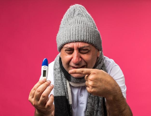 Weinender erwachsener kranker kaukasischer mann mit schal um den hals, der eine wintermütze trägt und auf das thermometer zeigt, das auf rosa wand mit kopienraum isoliert ist