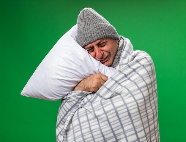 Weinender erwachsener kranker kaukasischer mann mit schal um den hals, der wintermütze trägt, die im karierten halten eingewickelt ist und kopf auf kissen setzt, das auf grüner wand mit kopienraum isoliert wird