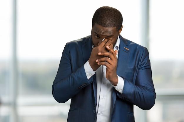 Weinender geschäftsmann, der sich die tränen abwischt. schwarzer mann in formeller kleidung weint und wischt sich die augen mit einer weißen serviette ab.
