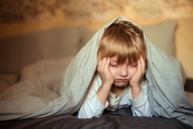 Weinender junge unter der decke auf dem bett