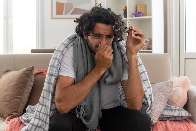 Weinender junger kranker kaukasischer mann, der in plaid mit schal um den hals gewickelt ist, eine optische brille hält und die hand auf die nase legt, die auf der couch im wohnzimmer sitzt