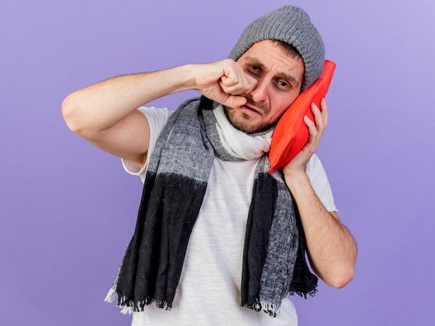 Weinender junger kranker mann, der wintermütze mit schal hält, der wärmflasche auf wange lokalisiert auf lila hintergrund hält