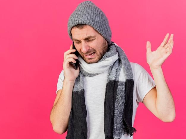Weinender junger kranker mann, der wintermütze mit schal trägt, spricht am telefon und hebt hand lokalisiert auf rosa hintergrund