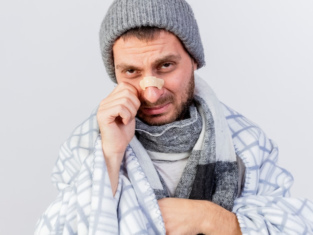 Weinender junger kranker mann, der wintermütze und schal trägt, eingewickelt in plaid mit gips auf nase lokalisiert auf weißem hintergrund
