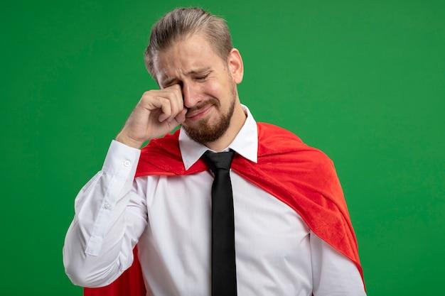 Weinender junger superhelden-typ, der auge mit hand lokalisiert auf grün abwischt