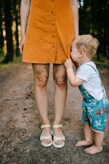 Weinender kleiner junge, der mit mamas beinen aufwirft