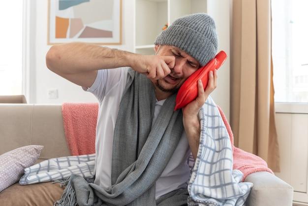 Weinender kranker mann mit schal um den hals, der eine wintermütze trägt und den kopf auf eine wärmflasche setzt, die auf der couch im wohnzimmer sitzt