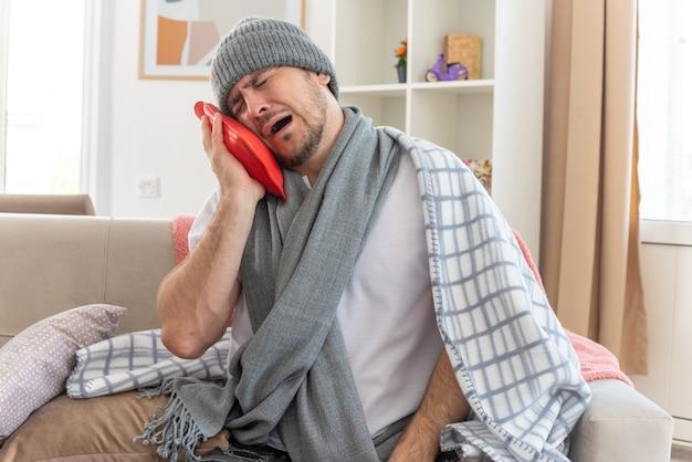 Weinender kranker slawischer mann mit schal um den hals, der eine wintermütze trägt, die in kariertes halten gewickelt ist und auf die wärmflasche schaut, die auf der couch im wohnzimmer sitzt